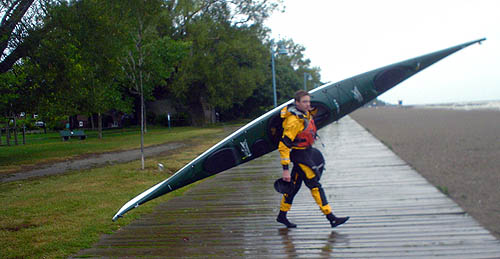Man in yellow-and-black outfit holds a helmet in one hand and a large green canoe over one shoulder as he crosses a damp beachfront boardwalk under cloudy skies
