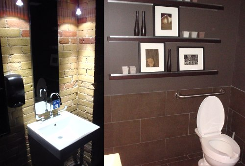 Well-decorated bathroom interior, with modern basin, exposed brick, and metal shelves with candles and knickknacks