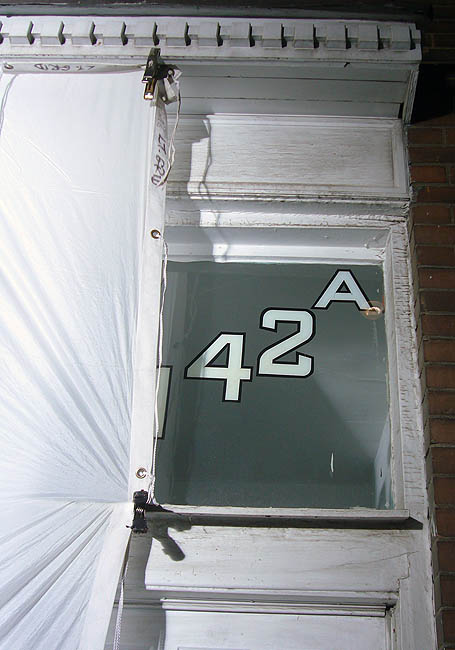White fabric screens cover everything but a brightly-lit house number over a door, 1142A