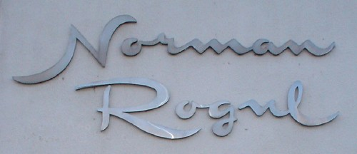 Stainless-steel letters read Norman Rogul in script, with large swash capitals and short lower-case letters