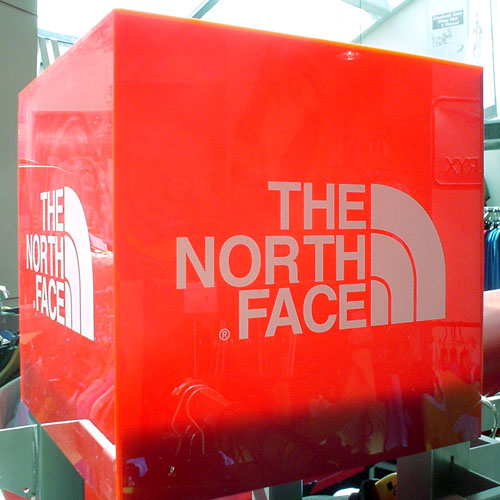 Red plastic cube, backlit by the sun, shows THE NORTH FACE logotype in Helvetica