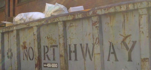 Stencilled letters on the side of a dumpster read NORTHWAY in Friz Quadrata
