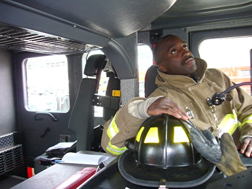 Black fireman inside cab of large fire apparatus, with helmet nearby
