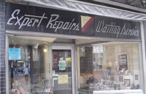 Sign over store reads Expert Repairs Waiting Service in script incised into granite