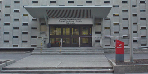Ontario Court of Justice building has giant concrete awning over entrance and a façade of white concrete dotted with short rectangular windows