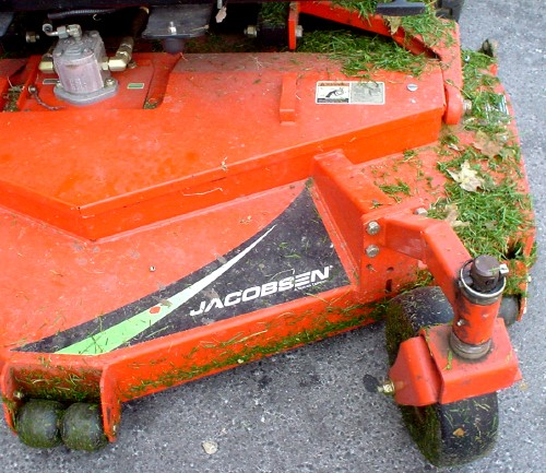 Orange Jacobsen lawnmower is dappled with green grass clippings