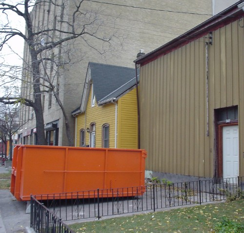 Bright-orange dumpster sits in an aluminum-sided building's driveway alongside mustard-coloured cottage
