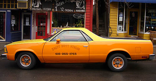 Orange-and-yellow El Camino, with HEAVY DUTY CYCLES written on the door in outlined blackletter and matching orange wheels, sits on a rainy street