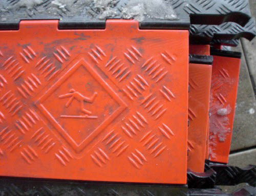 Orange plastic tread has debossed traction patterns and a pictogram of a person slipping headfirst on a flat surface