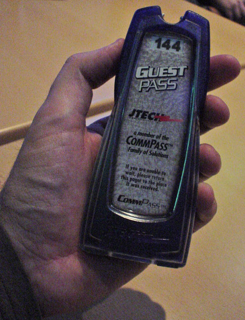 Narrow, palm-sized plastic pager numbered 144 reads 'Guest Pass JTech... If you are unable to wait, please return this pager to the place it was received. CommPass™'