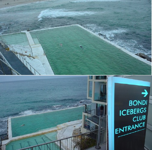 Deep-green swimming pool juts out into dark-green bay. Illuminated ice-blue sign reads 'Bondi Icebergs Club Entrance'