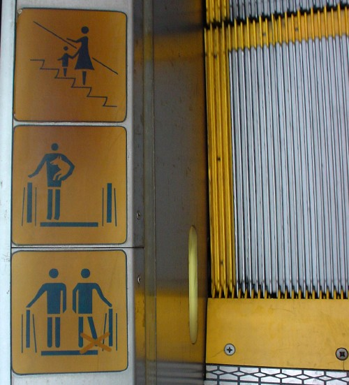 Three warning images at base of escalator treads: Female figure holding hand of child; male figure holding front half of some animal; and identical male figures, one of whose extended legs is overwritten with a red X