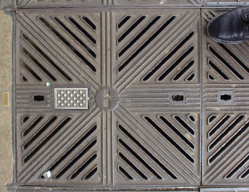 Toe of black Doc Marten boot encroaches on iron grating with diagonal grille