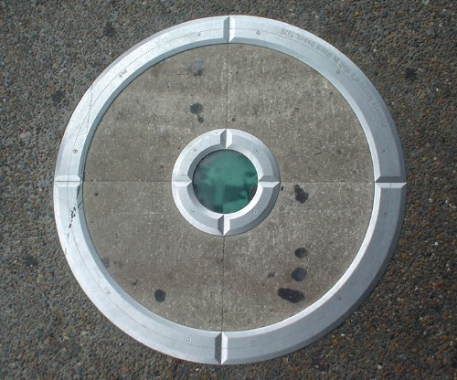 Metal rim embedded in sidewalk encloses four quadrants of concrete, a smaller rim, and a cloudy, emerald-green glass disc
