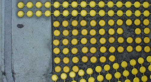 Raised yellow rubber dots are embedded in asphalt, extending into nearby concrete