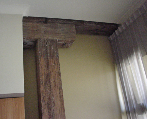 Foot-thick exposed-wood column intersects with joist at finished ceiling
