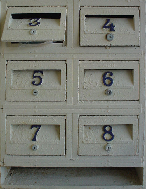 Six narrow mailboxes, with white stucco fronts, are labeled 3 through 8 in steel numerals