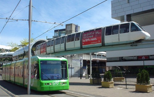On a sunny day, a monorail train curves overhead as green streetcar approaches at ground level