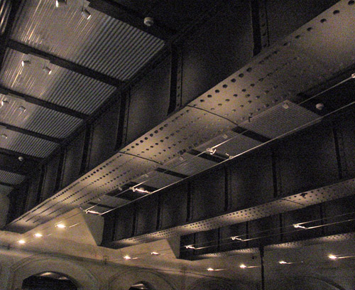 Thick, riveted I-beams line a ceiling