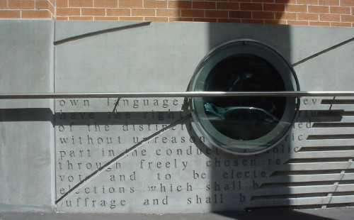 Concrete wall on brick building features large round glass porthole, stainless-steel barre, and inscriptions in the concrete in letterspaced lower-case Times