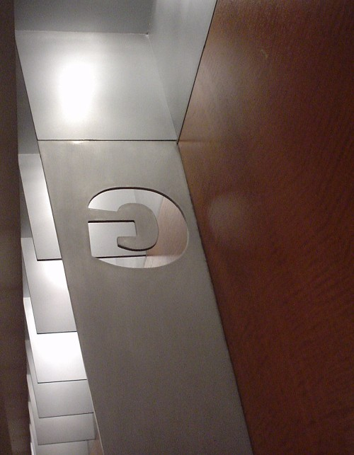 A Univers Bold 'G,' die-cut in an aluminum blade running top to bottom against a wooden wall, seen from behind