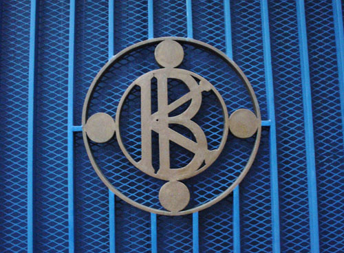 Molded brass plate shows a K and B superimposed on each other inside a circle, all attached to a dark-blue fence