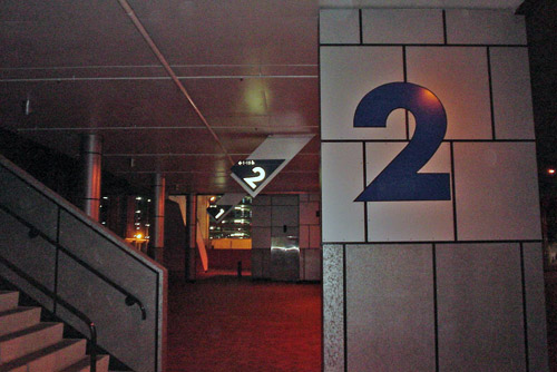 Parking-lot signage shows large Futura numeral 2s, upright on tile column in foreground and at an angle projecting from ceiling in background