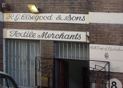 Hand-calligraphed signs on brick storefront read 'R.G. Elsegood & Sons Textile Merchants'