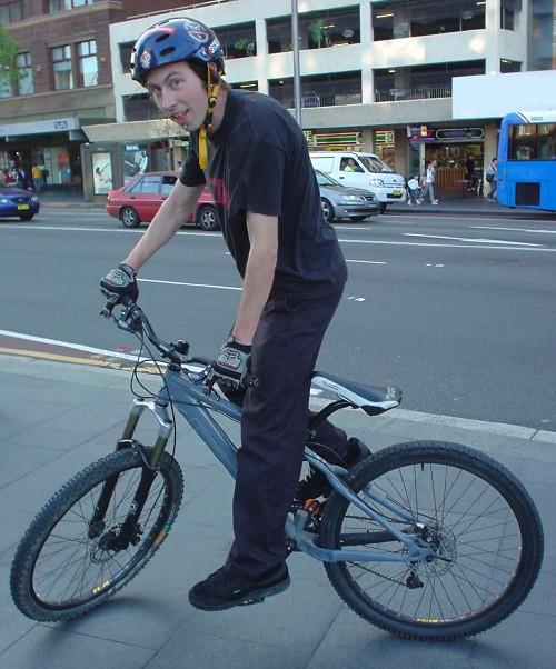 On a sidewalk, a teenage boy balances a trackstand on his bike