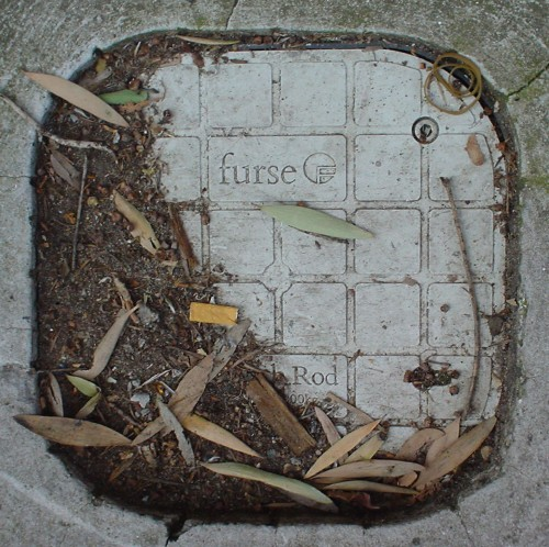 Square metal access lid is partly covered by dirt and leaves and has rounded corners, an embossed crisscross pattern, and the word 'furse' in Garamond type