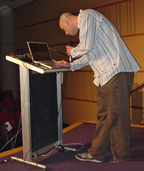 Dean Jackson leans to inspect PowerBook at podium