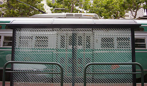 Green streetcar viewed through transit shelter with diagonal white stripes across its window