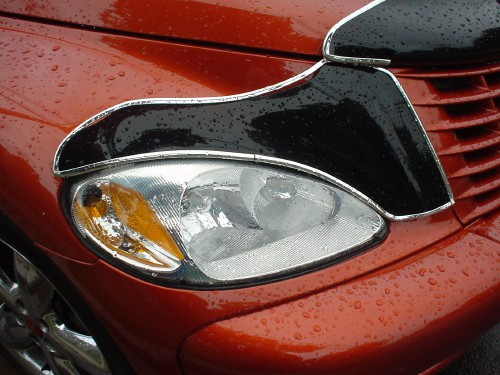 Bronze-coloured, rain-dappled PT Cruiser headlamp is surrounded by silver-edged black bra