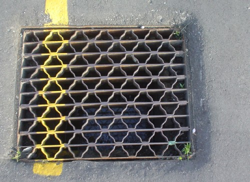 Metal grate has the same yellow stripe as the tarmac around it