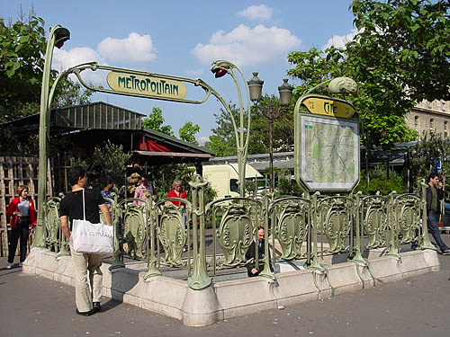 Staircase descending from sidewalk is labelled METROPOLITAIN in a typeface with varying capital heights. The entrance is surrounded by green wrought-iron shields