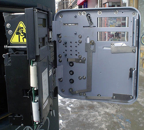 Metal door is swung open from control panel and faceplate, with yellow warning label on the side showing a man hitting his head against that door