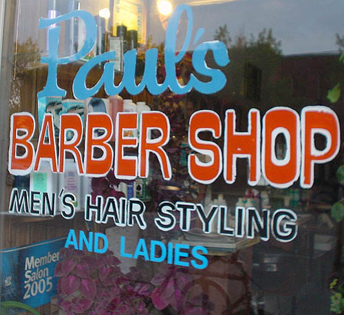 Hand-lettering on shop window reads Paul's BARBER SHOP MEN'S HAIR STYLING AND LADIES