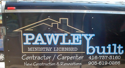 Side of glossy black trailer reads PAWLEY built in blue type, with 'Contractor / Carpenter' and phone numbers