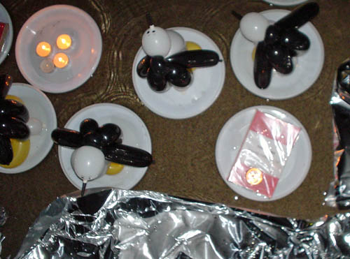 Paper plates holding model penguins made out of black, white, and yellow balloons float alongside other plates carrying a plastic-wrapped book and votive candles