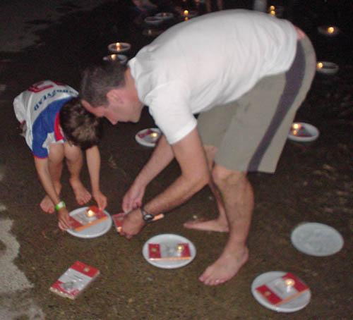 A man and a boy lean over and move two books and a candle on a floating paper plate