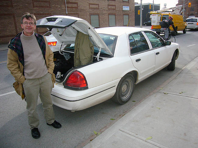 Many standing by opened trunk door of a white Crown Vic