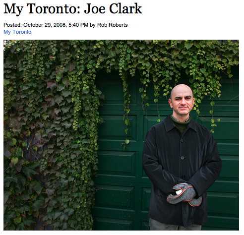 Me in black jacket and grey mitts before green garage door. Title: My Toronto: Joe Clark