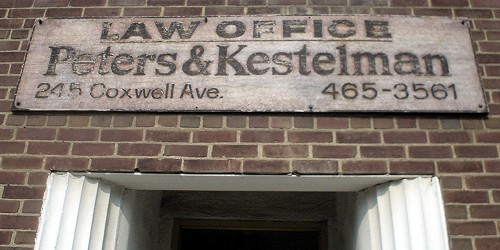 Weathered sign on brick wall above doorway reads LAW OFFICE Peters & Kestelman 245 Coxwell Ave.