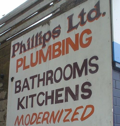 Hand-drawn sign reads Phillips Ltd. PLUMBING BATHROOMS KITCHENS MODERNIZED