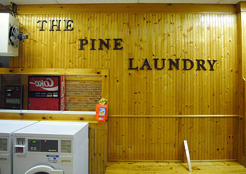 Butterscotch-coloured wall panelling behind washing machines is labelled THE PINE LAUNDRY in woodenletters