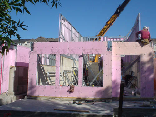 Workman sits on top edge of pink-insulation-covered wall at construction site