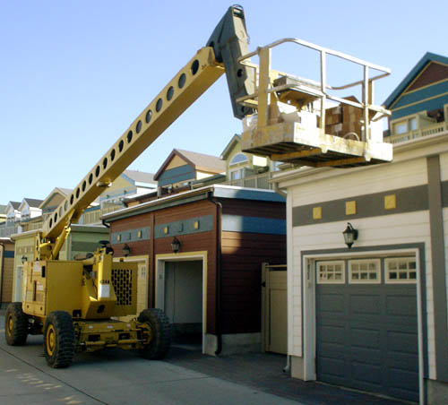 Crane holds its bin aloft on the end of a long yellow arm while parked in a laneway behind houses painted white/teal and brown/teal