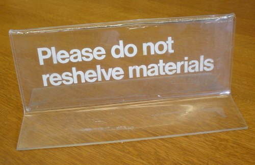 'Please do not reshelve materials' in white Helvetica on a clear Lucite desk notice