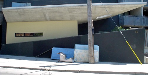 Mattresses and an old armchair lie on the sidewalk outside a building with angled walls, ramps, and awnings made of black, cream, and untinted concrete