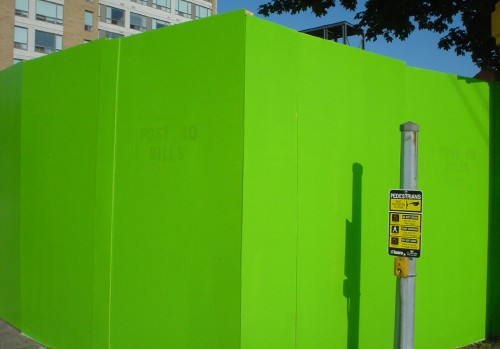 Next to a crosswalk post, a POST NO BILLS sign barely pokes through the hoardings' bright-green paint